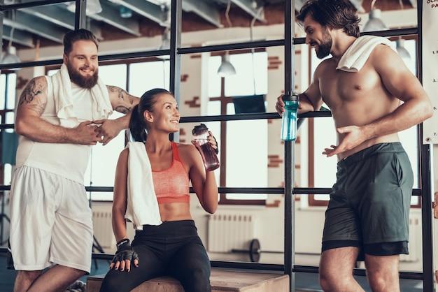 Silny facet rozmawia z ludźmi na siłowni.