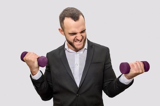 Silny i dobrze zbudowany młody człowiek w garniturze stoi i trzyma w dłoniach dwa hantle. ciężko ćwiczy.