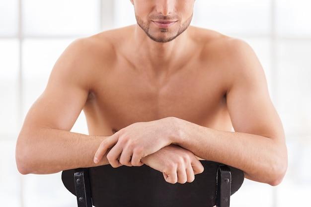 Silny i pewny siebie. przycięty obraz przystojnego młodego muskularnego mężczyzny siedzącego na krześle