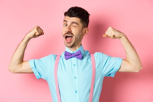 Silny i zabawny facet z francuskimi wąsami, napinający bicepsy i mrugający do kamery, popisujący się swoimi mocnymi stronami, stojący na różowym tle.