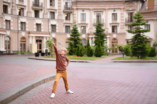 Silny, inteligentny i zabawny mały chłopiec bawi się na zewnątrz, w okularach.