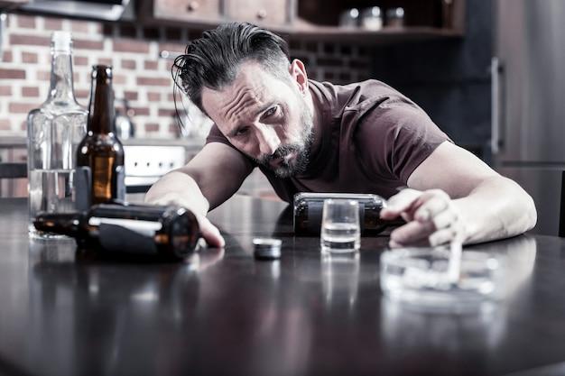 Silny kac. beztroski nieszczęśliwy pijak siedzący przy stole i budzący się z silnym kacem
