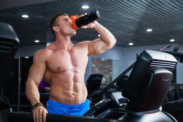 Silny kulturysta mięśni robi ćwiczenia cardio na bieżni. sportowiec pije wodę z wytrząsarki sportowej na nowoczesnej siłowni