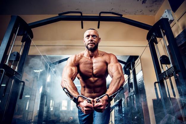Silny kulturysta robi ćwiczenia na siłowni