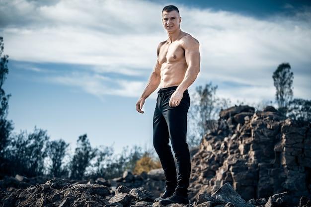 Silny kulturysta stojący na skale z nagim torsem. słoneczny dzień i błękitne niebo nad człowiekiem.
