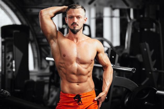 Silny kulturysta wygląda prosto, umięśniony kulturysta przystojni mężczyźni wykonujący ćwiczenia na siłowni