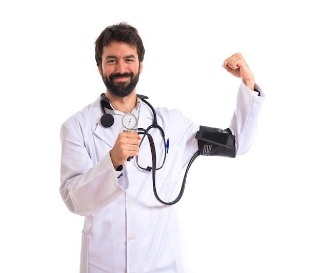 Silny lekarz z monitorem ciśnienia krwi na białym tle