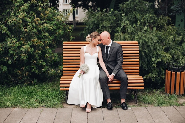 Silny mąż trzyma rękę swojej młodej żony i uśmiecha się
