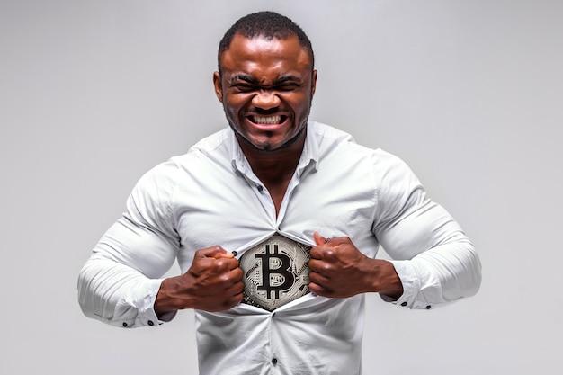 Silny męski biznesmen z afryki rozrywa koszulę. pod koszulką widoczny jest bitcoin
