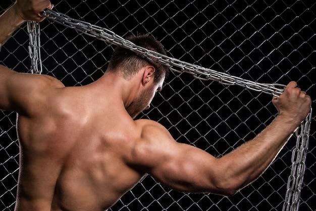Silny mężczyzna na ogrodzeniu z łańcuchami