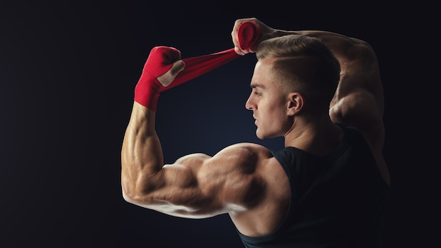 Silny mężczyzna owija ręce na czarnym tle mężczyzna owija ręce czerwonymi okładami bokserskimi na czarnym tle silne dłonie i pięści, gotowe do treningu i aktywnego ćwiczenia