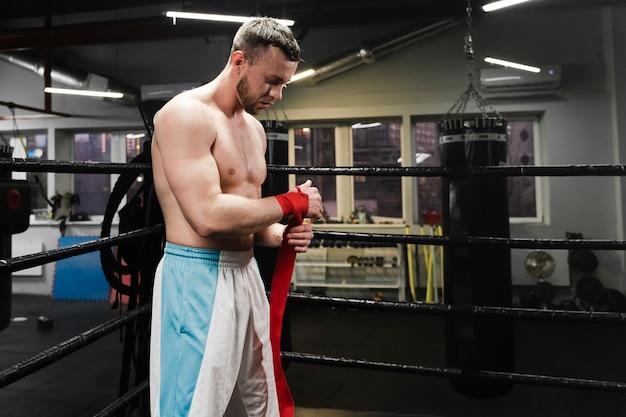 Silny mężczyzna przygotowuje się do treningu w ringu