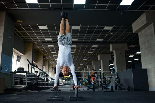 Silny mężczyzna robi ćwiczenia, trening fitness w siłowni