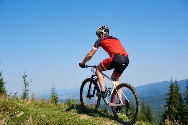 Silny mężczyzna rowerzysta turystyczny jazda rowerem na trawiastym wzgórzu. góry i błękitne letnie niebo w tle. aktywny styl życia i sport ekstremalny