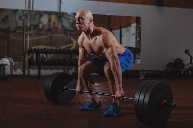 Silny mężczyzna sportowiec crossfit ćwiczenia z ciężką sztangą