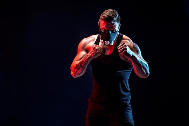 Silny mężczyzna sportowiec w czarnej masce treningowej na czarnej ścianie