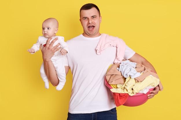Silny mężczyzna w białej casualowej koszulce, trzymając w rękach noworodka i umywalkę, robi pranie