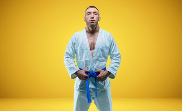 Silny mężczyzna w kimono z niebieskim paskiem. żółte tło. koncepcja sztuk walki. różne środki przekazu