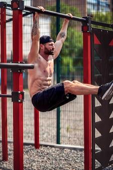 Silny mięśni brodaty mężczyzna robi ćwiczenia brzucha na drążku w parku lato