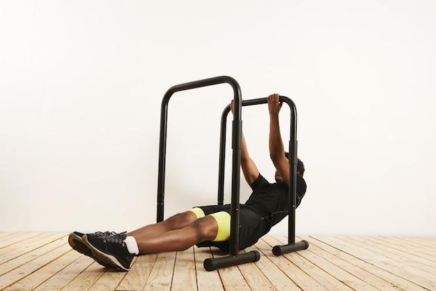 Silny, młody, czarny mężczyzna ubrany w czarną odzież sportową z jaskrawożółtymi pół rajstopami w pozycji wyjściowej do rzędów wagi ciała na czarnych mobilnych drążkach ustawionych na jasnej drewnianej podłodze przy białej ścianie.