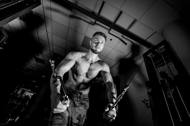 Silny młody człowiek z pięknym atletycznym ciałem robi ćwiczenia w siłowni. fitness, kulturystyka. opieka zdrowotna.