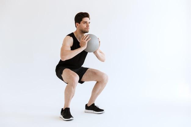 Silny młody sportowiec zrobić przysiady ćwiczenia z piłką na białym tle.