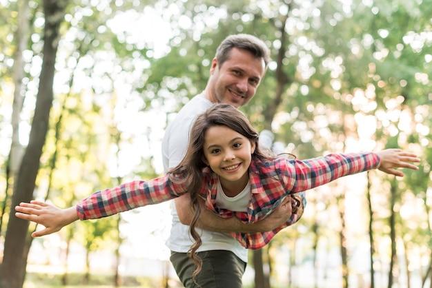 Silny ojciec niesie jego córki przy parkiem