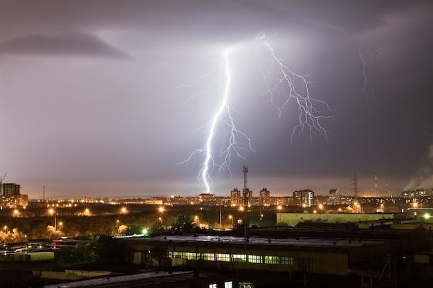 Silny piorun uderzający w ciemnoszare niebo uderza w ziemię, oświetlając okolicę przemysłową.
