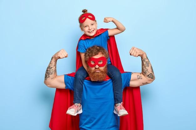 Silny, potężny tata i mała dziewczynka na ramionach pokazują mięśnie