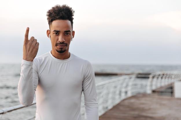 Silny poważny kędzierzawy brunetka mężczyzna w białej koszulce z długimi rękawami słucha muzyki w słuchawkach i wskazuje w pobliżu morza