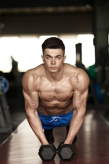 Silny, przystojny mężczyzna robi pompki na hantlach na siłowni jako ćwiczenia kulturystyczne, trenuje mięśnie