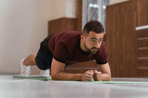 Silny, przystojny, młody człowiek, ćwicząc, robi deski w pustej siłowni lub w domu. umięśniony sportowiec wykonujący samodzielnie ćwiczenia podczas dystansu lub blokady na siłowni. zdecydowany facet na treningu fizycznym.