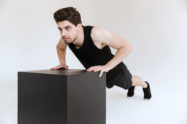 Silny skoncentrowany młody sportowiec na białym tle zrobić pompki do ćwiczeń na ramiona.