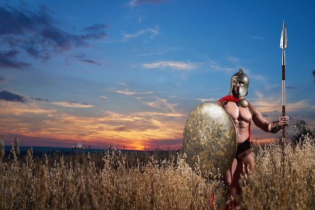 Silny spartański wojownik w stroju bojowym z tarczą i włócznią