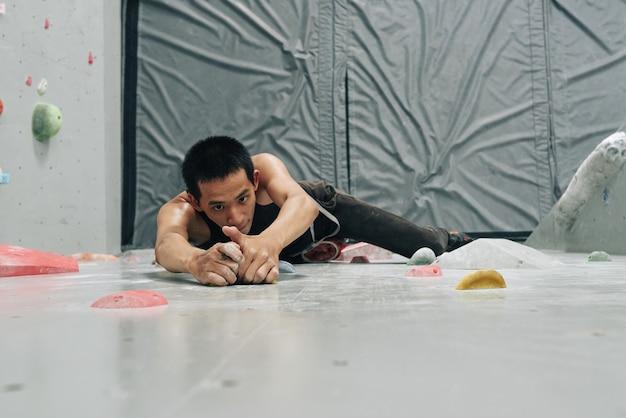 Silny sprawny mężczyzna wspinający się po ścianie bulderowej podczas treningu na ścianie bulderowej