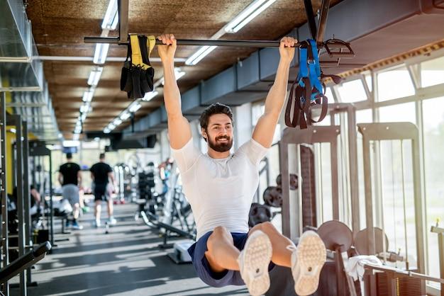 Silny szczęśliwy skoncentrowany sportowy mężczyzna ćwiczy w jasnej siłowni.