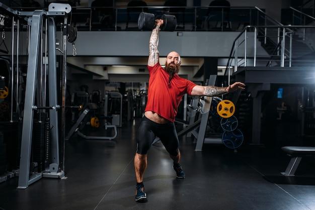 Silny sztangista z hantlami, trening na siłowni