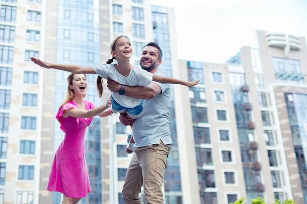 Silny tata. zachwycony miły mężczyzna trzymający swoją córkę podczas zabawy z nią