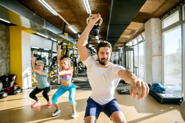 Silny, umięśniony, przystojny młody trener osobisty wykonujący ćwiczenia z kettlebells z dwoma aktywnymi sportowcami fitness w słonecznej nowoczesnej siłowni.