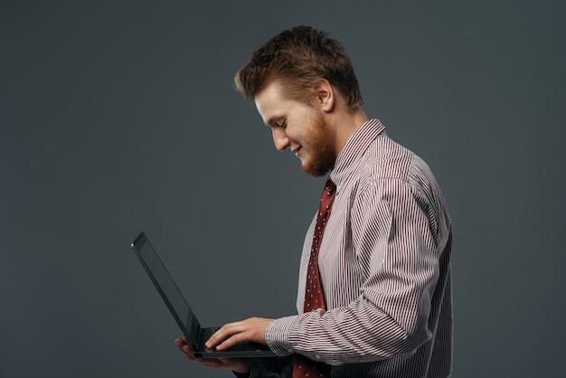 Silny wiatr wiejący na człowieka z laptopem, śmieszne emocje. potężny przepływ powietrza wieje na biznesmena na czarnym tle