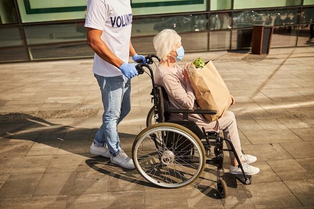 Silny wolontariusz obsługujący wózek inwalidzki seniora w drodze powrotnej ze sklepu z zakupami