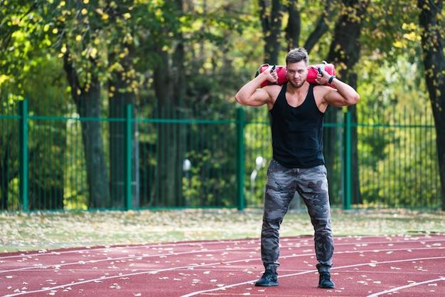 Silny wysportowany mężczyzna w sportowej odzieży treningowej 10-kilogramowy worek na ramiona na zewnątrz
