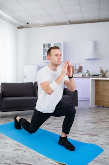 Silny wysportowany mężczyzna w t-shircie ćwiczy w swoim przestronnym mieszkaniu o minimalistycznym wnętrzu. zdrowy styl życia w okresie kwarantanny. fitness w domu