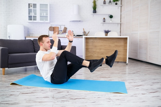 Silny wysportowany mężczyzna w t-shircie i ćwiczący prasę w domu w swoim przestronnym i jasnym mieszkaniu o minimalistycznym wnętrzu. uprawianie sportu w domu.