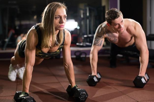 Siłownia mężczyzna i kobieta push-up pushup siły z hantle w treningu fitness