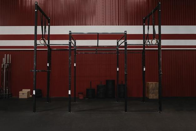 Siłownia ze sprzętem do ćwiczeń. drążki poziome, kółka gimnastyczne. wnętrze siłowni w kolorze czerwonym garażu.
