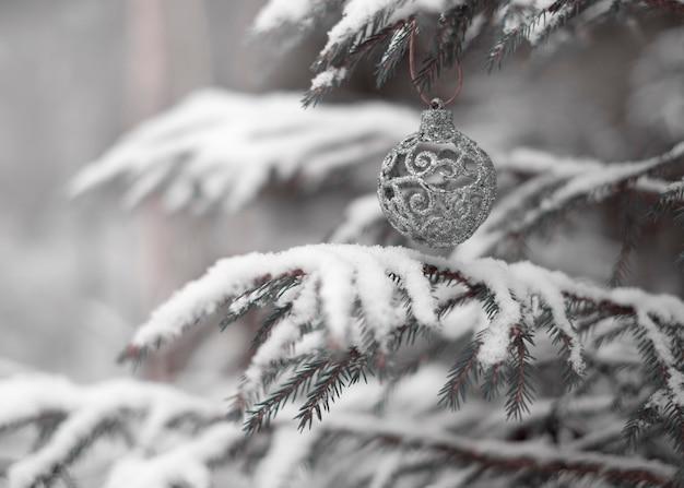 Silver christmas ball na naturalnym drzewie w zaśnieżonym lesie