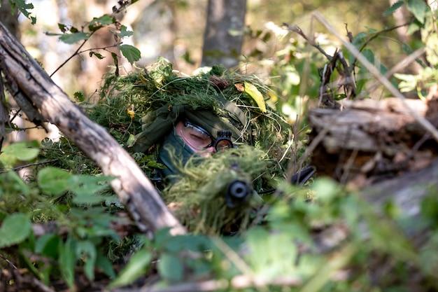 Siły specjalne, karabin szturmowy żołnierza z tłumikiem, celownik optyczny. za zasłoną czeka w zasadzce