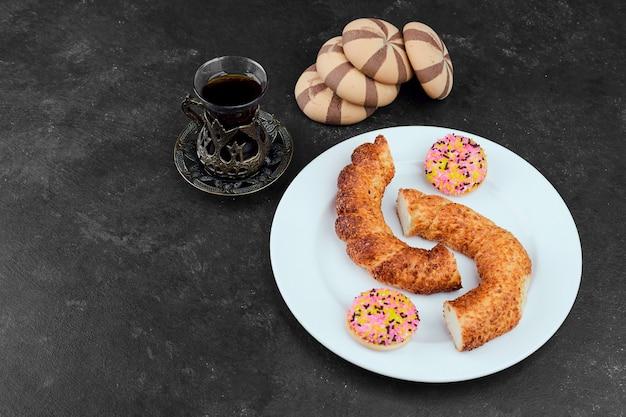 Simit, ciasteczka francuskie, ciastka kakaowe i szklanka herbaty na czarnym stole.