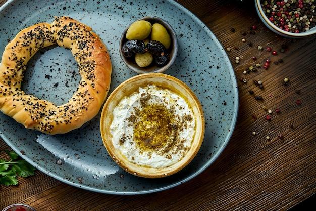 Simit z musem z sera feta z oliwą i przyprawami, podawany na niebieskim talerzu z oliwkami. tło drewna. bajgiel